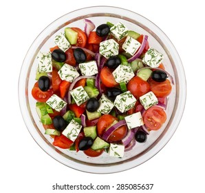 Transparent glass bowl with Greek salad isolated on white background, top view