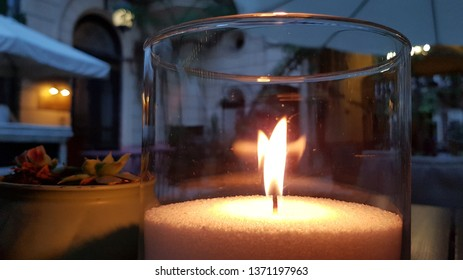Transparent glass candle holder with flame inside. Burning fire of candle on table. Blurred reflection of glowing candle flame in glass surface. Cozy evening still life with candlestick on foreground