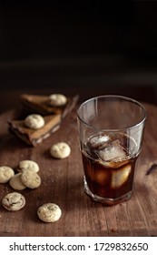 Transparent glass with cold coffee, sweets and cookies on a wooden table