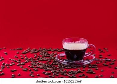 Transparent glass Cup with black coffee and scattered coffee beans on a red background.