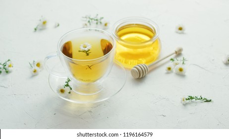 Transparent glass cup with herbal camomile tea and fresh flowers on table with jar of honey and wood stick