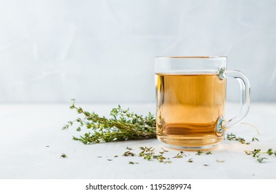 Transparent glass cup of herbal tea with thyme and sprigs of thyme tied in a bunch on a white background. Space for text.