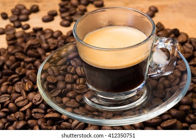 A transparent glass cup of hot espresso on a saucer standing on a wooden table top, surrounded by coffee beans