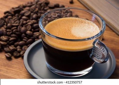 A transparent glass cup of hot espresso on a saucer standing on a wooden table top, surrounded by coffee beans and a vintage book