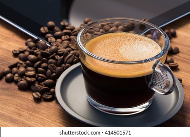 A transparent glass cup of hot espresso on a saucer standing on a wooden table top, surrounded by coffee beans and an tablet in the background