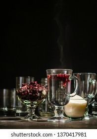 Transparent glass Cup with hot red tea from hibiscus or hibiscus. Glassware and dry petals with sugar