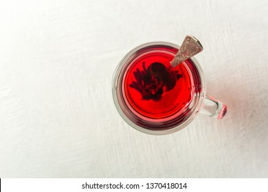 Transparent glass Cup with hot red tea from hibiscus or hibiscus. Copy space.