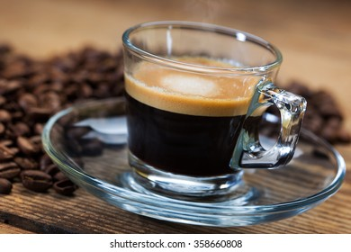 A transparent glass cup of hot steamy espresso on a saucer standing on a wooden table top, surrounded by coffee beans