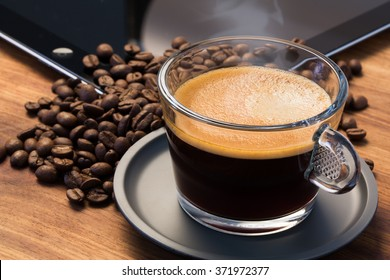 A transparent glass cup of hot steamy espresso on a saucer standing on a wooden table top, surrounded by coffee beans and an iPad in the background