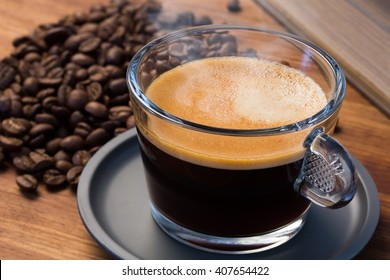 A transparent glass cup of hot steamy espresso on a saucer standing on a wooden table top, surrounded by coffee beans and a vintage book