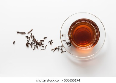 transparent glass cup with tea on the saucer with dry tea leaves on a white background