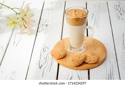 Transparent glass of Dalgona coffee, the Korean coffee drink made of hot or cold milk topped with whipped instant coffee, sugar and hot water mixture.
