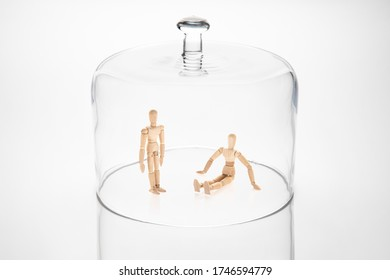 Transparent glass dome with two wooden mannequins within. One standing and the other seated on the ground. They illustrate the lockdown due to an exterior factor.