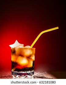 transparent glass  with ice cubes in the form of star and cola with a variety of colored  pipe tubes on red background. Space for inscriptions. food and drink background. cool beverage