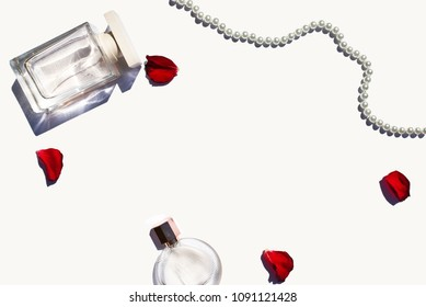 Transparent glass perfume bottles, pearl necklace and red rose petals on white background.