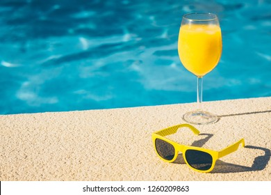 Transparent glass with a refreshing drink - an alcoholic cocktail or smoothie and yellow trendy glasses on the edge of the pool - copy space
