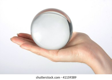 The transparent glass sphere lies on a female palm