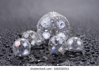 Transparent glass sphere with water drops isolated on black background