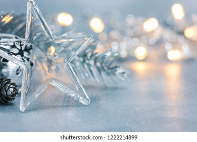 transparent glass star with christmas jingle bell and fir tree branch on blurred silver background with glowing garland lights. macro view