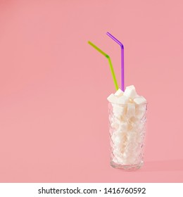 Transparent glass with straw full of sugar cubes on pastel pink background. Unhealthy food concept. Minimal, vertical, side view.