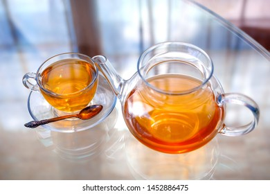 Transparent glass tea cup and pot with spoon on glass table in strong backlit
