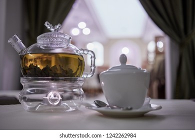 Transparent glass teapot on candle heater and sugar bowl with teaspoon, focus on teapot.