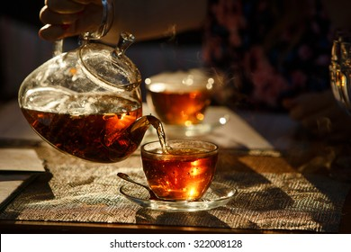 From transparent glass teapot pour black tea in glass mug, glows in the sun the last rays