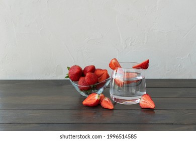 Transparent glass of water with slice of strawberries, cutted starwberries and berries in little plate and  on dark wooden table, copy space. Refreshing vitamin detox concept