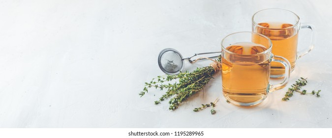 Transparent glasses cup of herbal tea with thyme and sprigs of thyme tied in a bunch on a white background. Web banner with copy space