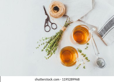 Transparent glasses cup of herbal tea with thyme and sprigs of thyme tied in a bunch on a white background. Top view.