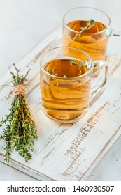Transparent glasses cup of herbal tea with thyme and sprigs of thyme tied in a bunch on a white background
