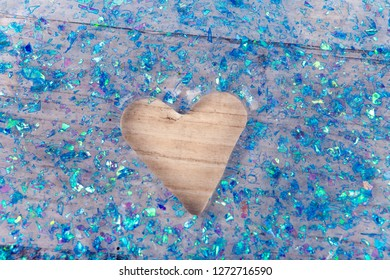 Transparent glitter slime with a heart shape hole on a wooden surface