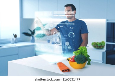 Transparent hologram. Calm confident man using futuristic technologies and touching the hologram while controlling his diet