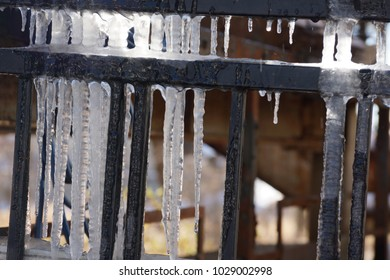 Transparent icicle is hanging from the fence.