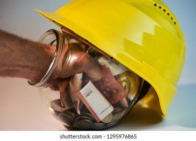 Transparent jar with money coins and bills inside it and an construction helmet on top of it with someone trying to get their hand out of the jar with a fist full of money