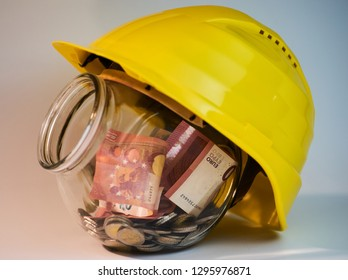 Transparent jar with money coins and bills inside it and an construction helmet on top of it with opened lid