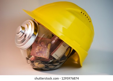 Transparent jar with money coins and bills inside it and an construction helmet on top of it with closed lid
