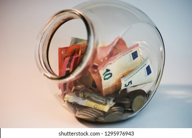 Transparent jar with money coins and bills inside it with opened lid