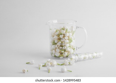 Transparent lab beaker and test tube filled with fresh white jasmine flowers with some jasmine spilled on white background