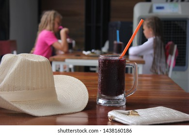Transparent mug with cold kvass on the table in the cafe near the hat against the background of cafe visitors. The concept of rest