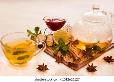 transparent mug with Lemon Tea, near raspberry jam, mint, ginger and cinnamon, glass brewery on wite bacground