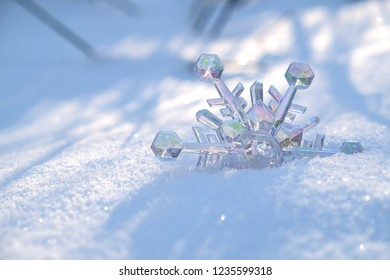 Transparent nacreous snowflake in snow. Christmas and New Year holidays background.