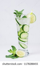 Transparent organic drink with slices cucumber, ice, lime, mint on white wood table.