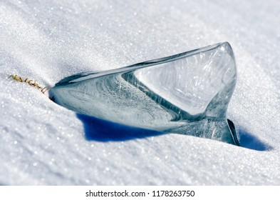 Transparent piece of ice on the snow near frozen Baikal lake