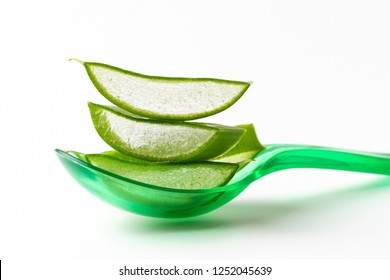 Transparent pieces of aloe vera leaf on a spoon a white background