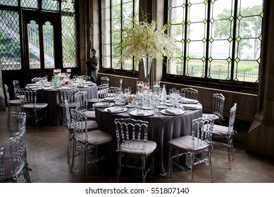 Transparent plastic chairs stand around dinner tables with dark grey cloth