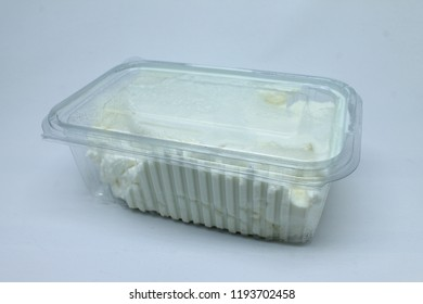 transparent plastic container with condensed yoghurt isolated on white background