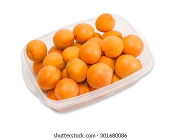 Transparent plastic tray with ripe apricot closeup on a light background. Isolation.