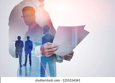 Transparent portrait of unrecognizable businessman looking at documents with double exposure of his colleagues and graph in the foreground. Toned image
