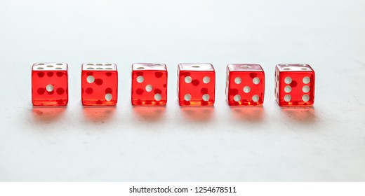Transparent red craps dices arranged on white board, showing all numbers from one to six. Front view.